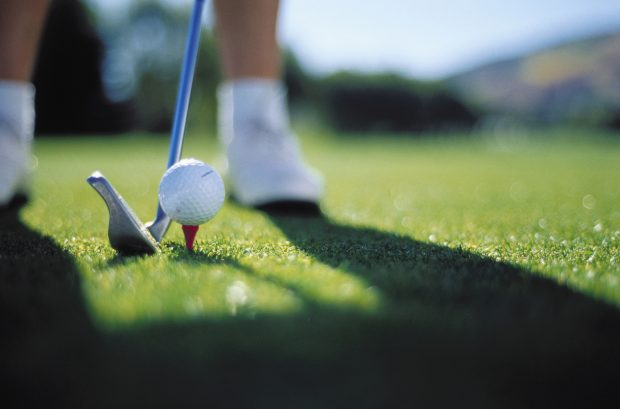 Close-up of a golf club near a golf ball on a tee