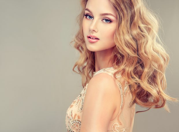 Young beautiful woman, dressed in evening gown. Loose,wavy hair and bright make up.Spring mood.