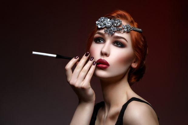 Beautiful young woman with smoky eyes and full red lips holding cigarette holder. Massive crystal hair accessory on head. Retro styling. Studio beauty shot. Copy space.