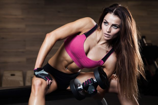 Young athletic woman working her biceps with heavy dumbbells
