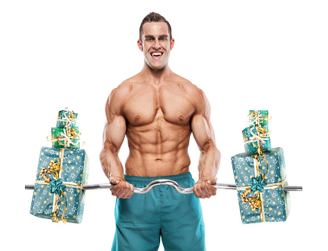 Muscular bodybuilder guy doing exercises with gifts