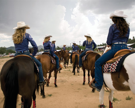 Cowgirls riding horses
