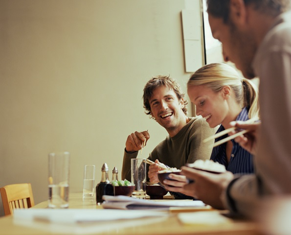 Young man having lunch with woman and man, smiling