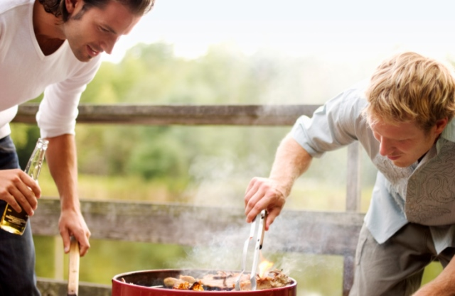 Two men grilling chicken