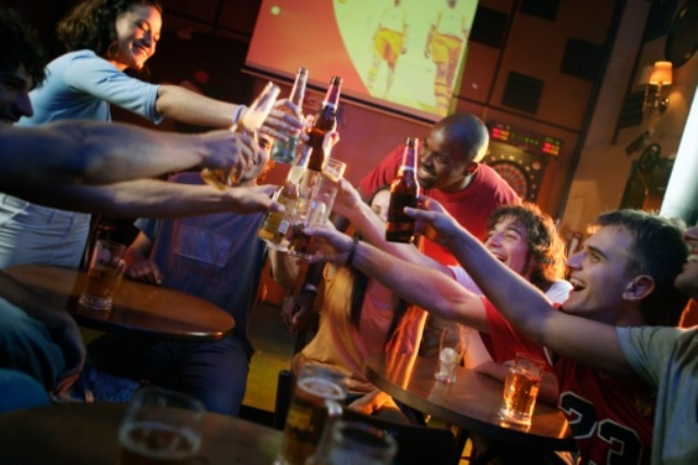 Soccer Fans and Young Adults Make a Toast in Bar