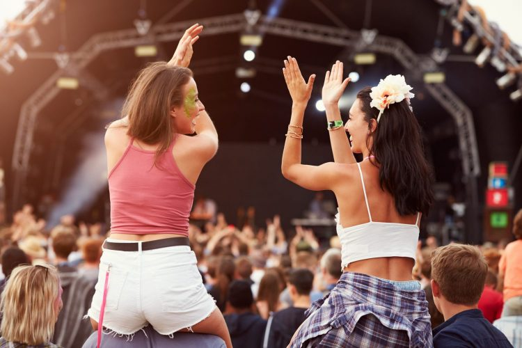 Two girls on shoulders in the crowd at music festival
