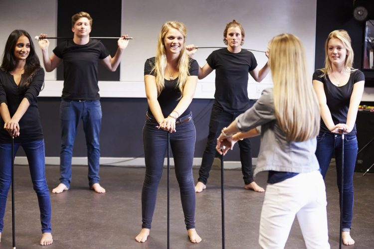 Students Taking Dance Class At Drama College Holding Dance Canes