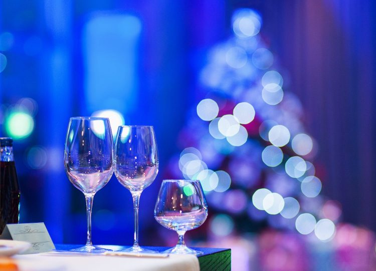 Empty glasses in restaurant with defocused Christmas tree