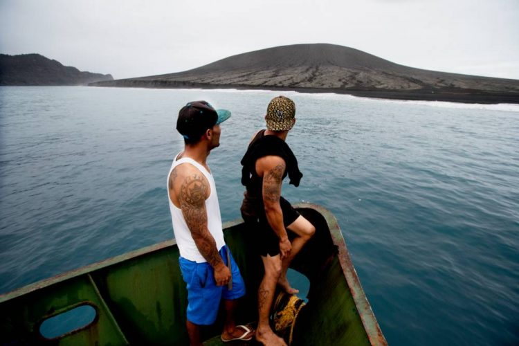 TONGA - JULY 10:  (AUSTRALIA & NEW ZEALAND OUT) Curious fisherman approach an unnamed land mass which is the newest island on Earth, July 10, 2015. The island emerged from the waters of the South Pacific in January 2015 when a volcano erupted on nearby Tonga, forcing pulverised magma into the air above the ocean. The magma gradually built up on the ocean floor, penetrating the surface of the water to form the island. (Photo by Edwina Pickles/The Sydney Morning Herald/Fairfax Media via Getty Images)